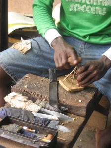 Adding raffia to form a handle for the adinkra stamp