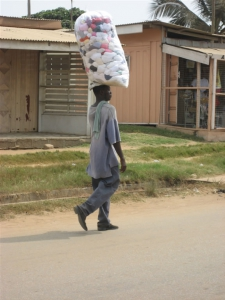 Man carrying a bag of laundry on his head