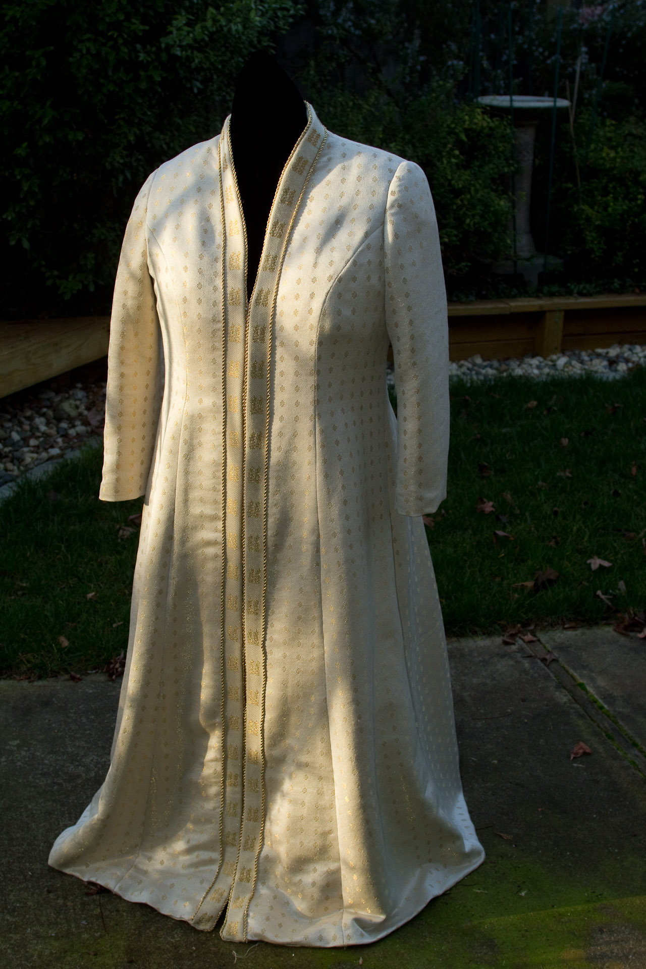 Handwoven wedding coat, draped over dress form