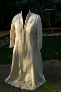 Handwoven wedding coat, draped over dress form