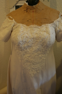 An interim view of the wedding dress, with pearls and lace still in the design stages.